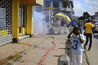 People walks through and protects their faces, ears while hundred meters length firecrackers exploding on a sidewalk in crowded street.....End of year 2010 celebrations on the streets of Paramaribo. Suriname is one of biggest consumer in South America that using firecrackers, fireworks ( also locally known as pagara ) for celebrations, especially for end of every years and also beginning of every new Chinese Years.