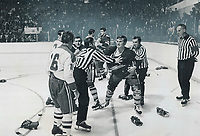 Fight night at gardens: Brawling broke out after only 22 seconds of hockey season at Maple Leaf Gardens last night. Leafs' Rickey Ley (2) tries to get past linesman Claude Bechard (22) to continue scuffle with Montreal's Henri Richard (16). In attempting to reach Richard, Toronto defenceman flung linesman to ice, for which he earned misconduct penalty. Referee John Ashley calmly watches.