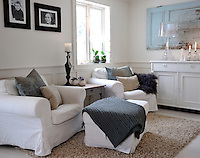 A cosy TV-watching area in the living room is furnished with large armchairs dressed with loose covers and patterned cushions
