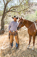 """2016 Best Freelance Editorial Photograph - American Horse Publications<br /> 2nd Place:  """"Andy Camacho with Sin Derella WP Taking a Break""""<br /> Published in Arabian Horse World, November 2015<br /> What the judges said:<br /> """"Really nice portrait of man with his horse.  Framed well by trees.  Man's face is not hidden by shadow of his hat.  Good focus."""""""