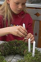 Kinder basteln einen Lichterkranz für die Adventszeit, Adventskranz, Kind steckt Kerze mit Draht in den Kranz