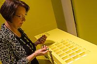 """Ausstellung """"Dialog mit der Zeit"""" im Museum fuer Kommunikation in Berlin-Mitte.<br /> Vom 1. April bis 23. August 2015 werden in der Ausstellung die Facetten des Alters und der Alterns erlebbar gemacht.<br /> Bundespraesident Joachim Gauck eroeffnete die Ausstellung am 31. Maerz 2015 mit einem Rundgang und einer Rede zu neuen Altersbildern in einer Gesellschaft des laengeren Lebens.<br /> Im Bild: Gudrun Loebert (geschrieben mit oe), 72. Sie ist eine der """"Senior-Guides"""" der Ausstellung. Hier fuehrt sie vor wie unter Stress Tabletten richtig sortiert werden muessen.<br /> 31.3.2015, Berlin<br /> Copyright: Christian-Ditsch.de<br /> [Inhaltsveraendernde Manipulation des Fotos nur nach ausdruecklicher Genehmigung des Fotografen. Vereinbarungen ueber Abtretung von Persoenlichkeitsrechten/Model Release der abgebildeten Person/Personen liegen nicht vor. NO MODEL RELEASE! Nur fuer Redaktionelle Zwecke. Don't publish without copyright Christian-Ditsch.de, Veroeffentlichung nur mit Fotografennennung, sowie gegen Honorar, MwSt. und Beleg. Konto: I N G - D i B a, IBAN DE58500105175400192269, BIC INGDDEFFXXX, Kontakt: post@christian-ditsch.de<br /> Bei der Bearbeitung der Dateiinformationen darf die Urheberkennzeichnung in den EXIF- und  IPTC-Daten nicht entfernt werden, diese sind in digitalen Medien nach §95c UrhG rechtlich geschuetzt. Der Urhebervermerk wird gemaess §13 UrhG verlangt.]"""