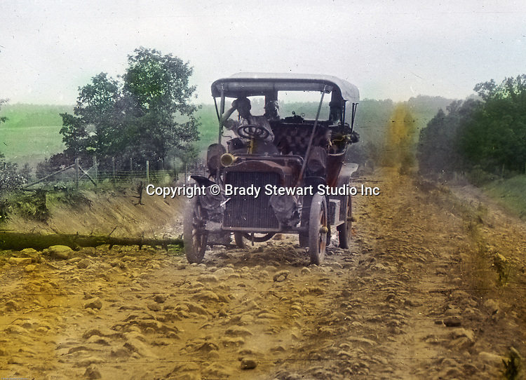 Greensburg PA:  The 1906 Buick Model F broken down after running over a tree on a rocky road outside Greensburg PA.  To give family and friends a better feel for the adventure, he hand-color black and white negatives into full-color 3x4 lantern slides.  The Process:  He contacted a negative with another negative to create a positive slide.  He then selected a fine brush and colors and meticulously created full-color slides.