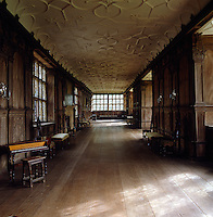 View down the length of the Long Gallery with its carved wood panelling and ornamented plaster ceiling