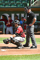 Kyle Pollock (9) of the Idaho Falls Chukars behind the plate with home plate umpire Ryan Powers during the game against the Ogden Raptors in Pioneer League action at Lindquist Field on July 27, 2014 in Ogden, Utah.  (Stephen Smith/Four Seam Images)