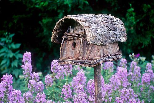 Handmade bark and woven birdbox, birdhouse, front view fancy set in garden among blooming purple flwoers