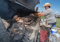 NWA Democrat-Gazette/J.T. WAMPLER Hannah Ciceroni of Rogers uncovers a whole alligator she cooked on charcoal overnight Sunday Oct.2, 2016 at the Downtown Rogers Farmers Market as a fundraiser for Main Street Rogers. Ciceroni harvested two gators and two wild hogs in south Texas last week. Local chefs cooked the fresh gators and hogs, each putting their own touches on the wild meat.