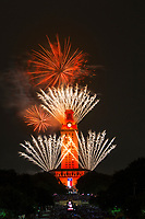 The UT Campus in downtown Austin, Texas, hosts the graduation ceremony in the Spring of 2017, culminating this celebratory fireworks as seen in this photograph of the UT Tower draped in vibrant burnt orange and stunning explosion of fireworks creating a stunning color display over the University of Texas campus in downtown Austin, Texas.