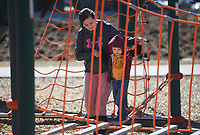 Sagan Gregory of Rogers (from left) helps Silas Hackett, 3, walk across a jungle gym, February 22, 2021 at Osage Park in Bentonville. Check out nwaonline.com/210223Daily/ for today's photo gallery. <br /> (NWA Democrat-Gazette/Charlie Kaijo)