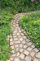 Stone garden bench in rustic country garden full of old-fashioned heirloom flowers, stone pavers in curving path, wide view