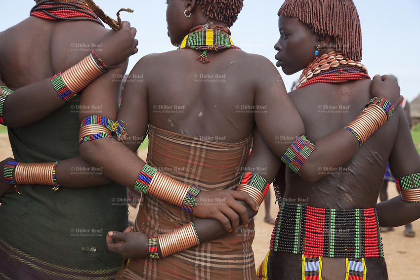Ethiopia. Southern Nations, Nationalities, and Peoples' Region. Omo Valley. Turmi. Hamar tribe (also spelled Hamer). Pastoralist group. Hamar women wear an elaborately decorated goatskin, often colored with beads and cowries. Beaded necklaces, bracelets and waistbands adorn their bodies. Hamer women indulge in elaborate hairdressing by decorating their hair with clay and butter twisted into a striking long plait. Thick scars coloured dull red and black cover the backs of women belonging to Ethiopia's Hamar tribe as a legacy of an initiation rite that sees them whipped and beaten bloody. The Omo Valley, situated in Africa's Great Rift Valley, is home to an estimated 200,000 indigenous peoples who have lived there for millennia. Amongst them are 60'000 to 70'000 Hamar, an Omotic community inhabiting southwestern Ethiopia. They live in Hamer woreda (or district), a fertile part of the Omo River valley, in the Debub Omo Zone of the Southern Nations, Nationalities, and Peoples Region (often abbreviated as SNNPR) which is one of the nine ethnic divisions of Ethiopia. 10.11.15 © 2015 Didier Ruef