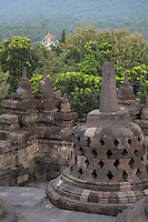 Borobudur, Java, Indonesia.  Stupas near the top of the Borobudur temple.  The diamond-shaped holes symbolize the passions that still linger as men rise toward Nirvana.  Monastery Stupa in the far distance.