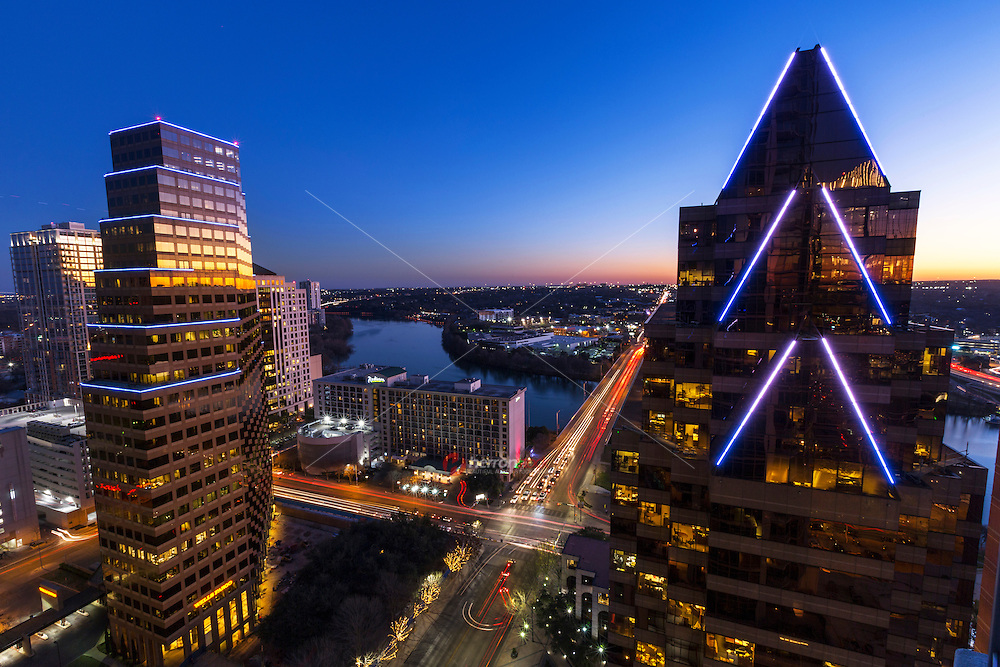 Aerial view as a beautiful violet and orange sunset falls on the downtown skyscrapers of the Austin Skyline as bright neon buildings light the clear night sky and the traffic below fills the Congress Avenue Bridge.