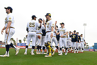 Michigan Wolverines players including Johnny Slater (25), Dominic Jamett (41) and Travis Maezes (9) congratulate each other after winning the first game of a doubleheader against the Siena Saints on February 27, 2015 at Tradition Field in St. Lucie, Florida.  Michigan defeated Siena 6-2.  (Mike Janes/Four Seam Images)