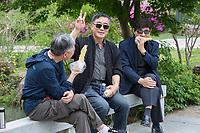 Yangzhou, Jiangsu, China.  Three Men Relaxing, Eating Corn on the Cob, Slender West Lake Park.