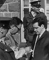 Checkpoints slow separatist boss; Quebec separatist leader Pierre Bourgault (left) stands by while police search his car for explosives and weapons while he was travelling to Quebec City for rally.<br /> <br /> 1964<br /> <br /> PHOTO :  Frank Grant - Toronto Star Archives - AQP