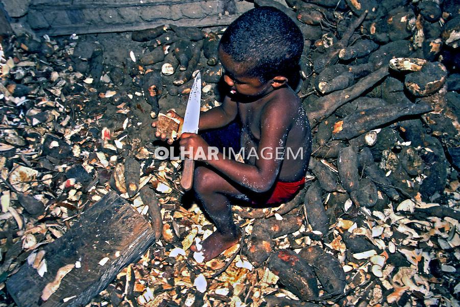 Menino descascando mandioca, Monte Pascoal, Bahia. 1999. Foto de Juca Martins...