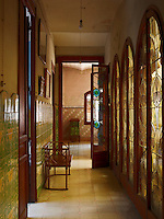 A tiled corridor is lit by arched stained glass windows