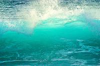 Backlit shorebreak wave.