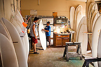 Surfboard shaper Eric Arakawa and employee discussing a surfboard at their factory in Waialua