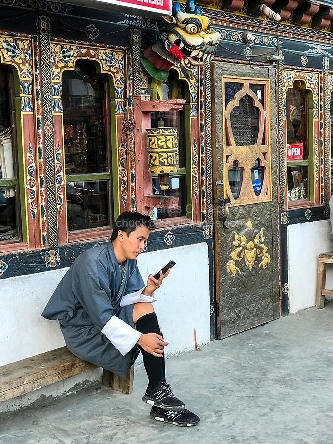 Jakar, Bumthang, Bhutan.  Young Man Weating Traditional Gho Checks his Cell Phone while Sitting below Prayer Wheel outside Entrance to a Store.