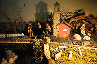 """Switzerland. Canton Tessin. Vira Gambarogno. The old town shows an exhibit of various Nativity scenes, illuminated at night for the Christmas holiday season. A Nativity Scene, may be used to describe any depiction of the Nativity of Jesus in art, but in the sense covered here, also called a crib or in North America and France a crèche (meaning """"crib"""" or """"manger"""" in French). It means a three-dimensional folk art depiction of the birth or birthplace of Jesus, either sculpted or using two-dimensional (cut-out) figures arranged in a three-dimensional setting. Christian nativity scenes, in two dimensions (drawings, paintings, icons, etc.) or three (sculpture or other three-dimensional crafts), usually show Jesus in a manger, Joseph and Mary in a barn (or cave) intended to accommodate farm animals. The scene includes the Magi or Three Wise Men (with or without a camel), shepherds and sheep, and the angels. Train and church.  © 2007 Didier Ruef"""