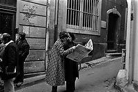 Devant le siège du Syndicat des Vignerons de l'arrondissement de Narbonne. 5 mai 1976. Deux femmes regardant le journal ; à gauche groupe de personnes. Cliché réalisé le lendemain des manifestations viticoles de Montredon-des-Corbières (Aude) lors desquelles deux personnes sont mortes : Emile Pouytes (vigneron d'Arquette-en-Val) et Joël Le Goff (commandant des CRS).