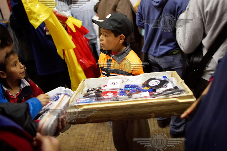 Children sell merchandise paraphernalia outside the wrestling stadium. Lucha Libre is a style of wrestling started in Mexico in 1933. The name means Free Fight, and matches tend to be focussed on spectacle and theatre with fans cheering for their favourite characters, who wear masks while jumping from the ropes, flipping opponents, and occasionally crashing into the crowd..