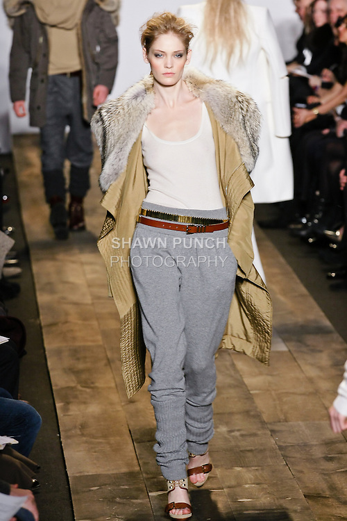 Heidi Mount walks the runway in a camel silk poplin utility coat, white tissue cashmere tank, and smoke cashmere sweatpant at the Michael Kors Fall 2010 runway fashion show, during Mercedes-Benz Fashion Week Fall 2010.