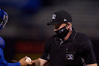 Umpire Austin Nelson, who is wearing a phone with the Automatic Ball-Strike System technology, checks the ball during a game between the Dunedin Blue Jays and Tampa Tarpons on May 7, 2021 at George M. Steinbrenner Field in Tampa, Florida.  (Mike Janes/Four Seam Images)