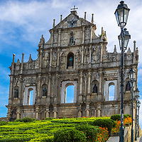 Perspective on the façade of the Saint Paul cathedral ruins with the garden in the foreground, under a cloudy, blue morning sky, in Macao, China