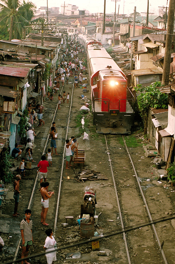 Manilla, Philippines, an afternoon train moves freight and passengers through the city. This aerial view is of an area where squatters have set up small houses (shacks) very close to tracks.