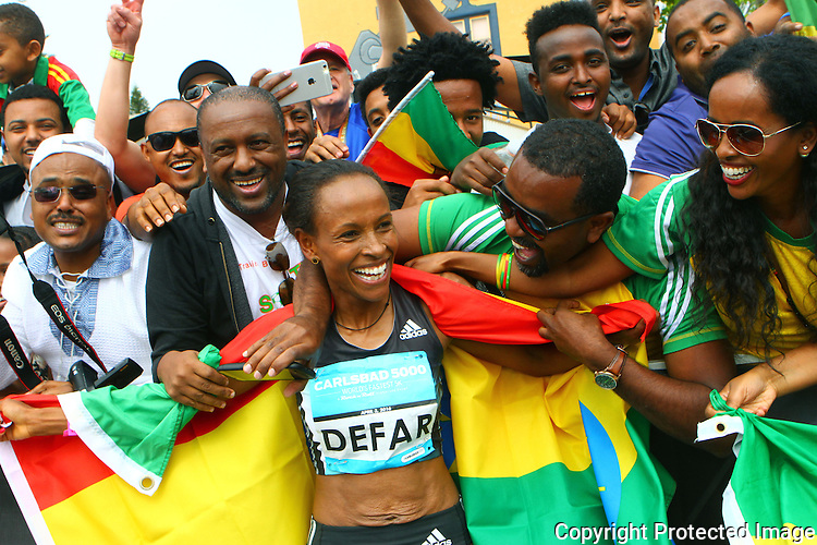 Meserat Defar of Ethiopia, who finished first in the Elite Women group of the Carlsbad 5000 Sunday, celebrates with fans after the race. photo by Bill Wechter