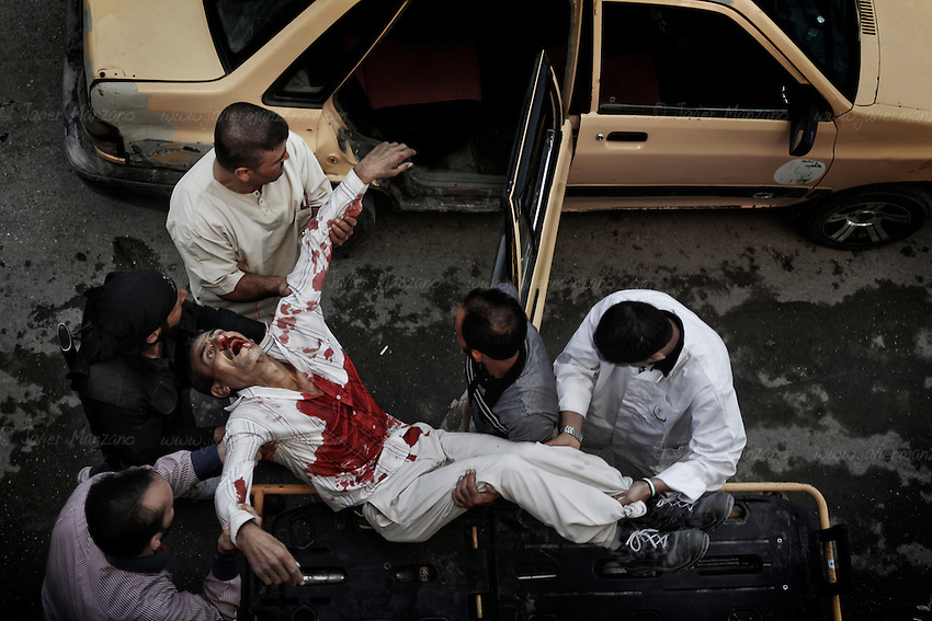 The body of a man shot dead by a government sniper is loaded onto a taxi for transportation to family members. Aleppo, Syria - October 2012...© Javier Manzano.