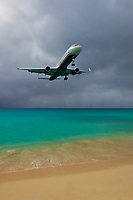 Plane landing at St Martin airport, just above the beautiful Maho Beach's golden sand and turquoise sea, in Sint Maarten, Caribbean Leeward Islands