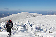 Winter hiker on the summit of South Twin Mountain in the White Mountains, New Hampshire during the winter months.