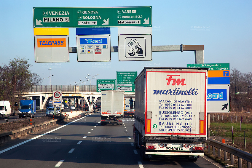 Italy. Lombardy region. Milan. Traffic signs, trucks and automobiles on a stretch of highway entering Milan by the Tangenziale Nord. Toll booths. Via card. 6.12.2011 © 2011 Didier Ruef