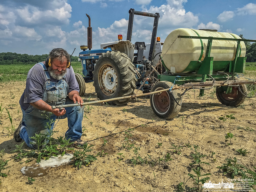 Farmer repairs spray nozzle while spraying herbicide to kill weeds in a soybean field where seeds failed to sprout in heavy spring rains.