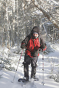 A hiker snowshoeing along the Mt Tecumseh Trail in the New Hampshire White Mountains during the winter months.