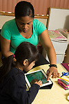 Education Preschool 4-5 year olds therapist teacher working with girl using iPad tablet
