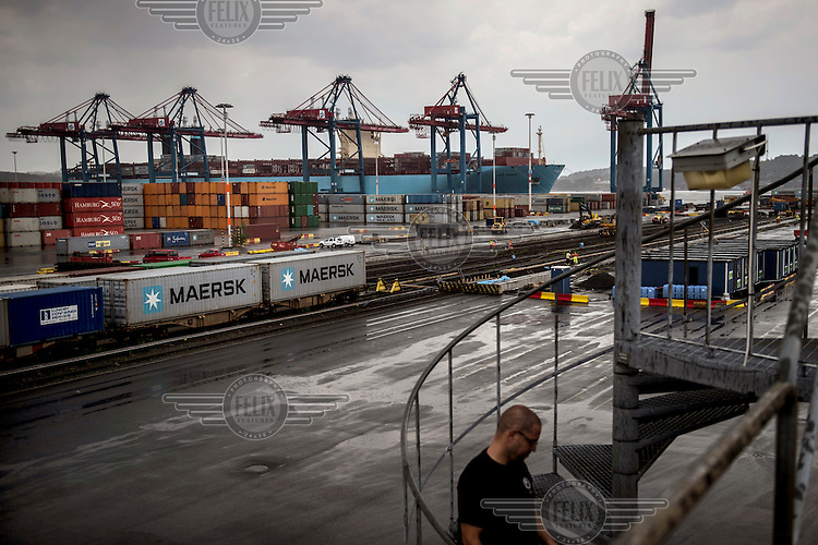A straddle carrier driver exits the cabin at the end of his shift while in the background the Mary Maersk, the largest container ship in the world, is loaded with containers.