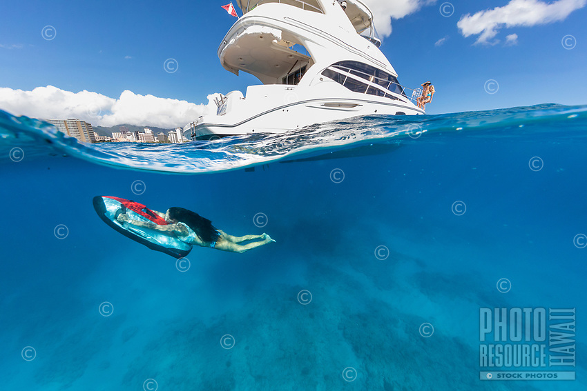 A woman rides an underwater sled around a power cruiser off of Waikiki, O'ahu.