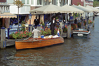 Wooden boat on an Amsterdam canal in front of a hotel and restaurant  The Netherlands, Holland