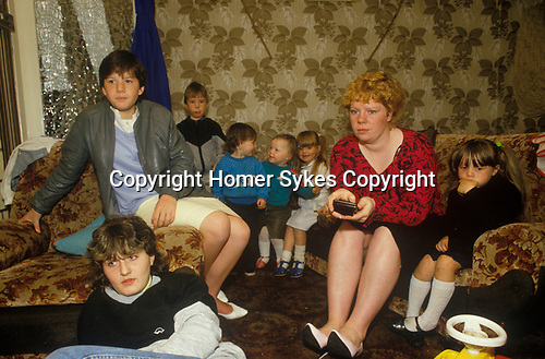 Glasgow, Scotland. 1980's<br /> Living on the Blackhill estate a young mother, a single parent with Zapper in hand watches TV with her seven young children.