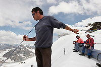 "A worker holds a safety line to a worker on Brunnenkogel Ferner.  It is wrapped with a fleece-like cover to keep it from melting.  Workers attached it to the top of the part of the glacier.  Covered ice melts slower. <br /> The ski area at 3,400 meters is covered to help save the ski industry since the glacier is retreating.  The cost of materials is one Euro per square meter.<br /> <br /> The Alpine glaciers -- in Austria, Switzerland, France and Italy -- are losing one percent of their mass every year and, even supposing no acceleration in that rate, will have all but disappeared by the end of the century. More hot, dry summers like that of 2003 in Europe, when the loss speeded to five percent, could cut the life expectancy to no more than 50 years, according to Wilfried Haeberli of the University of Zurich...""We estimate that by the end of the 21st century, with a medium-type climate scenario, about five percent of what existed in the 1970s will have survived, he added."
