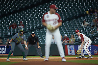 Heston Kjerstad (18) of the Arkansas Razorbacks holds runner Jared McKenzie (18) of the Baylor Bears on first base as starting pitcher Kole Ramage (28) comes to a set position during game nine of the 2020 Shriners Hospitals for Children College Classic at Minute Maid Park on March 1, 2020 in Houston, Texas. The Bears defeated the Razorbacks 3-2. (Brian Westerholt/Four Seam Images)