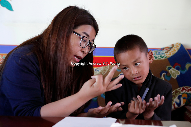 Lhasa, Tibet, China - Tibetan educator Deqingyuzhen teaches a young student mathematics during free classes at a community centre in Lhasa, September 2018.