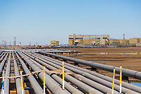 A series of pipes transport oil to an industrial complex in Prudhoe Bay, Alaska, on the arctic coastal plain.