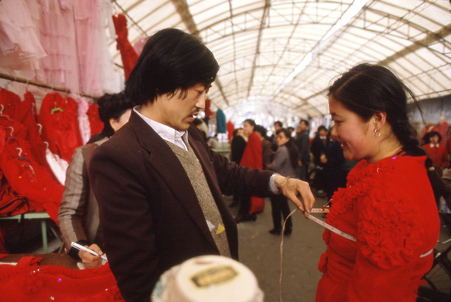 """Copyright Jim Mendenhall 1989. Day in the Life of China. Qing Dao. China on April 15. 1989. A bride if fitted for her gown in the street market """"Enterprise Zone,"""" which was part of China's experiment in government sanctioned capitalism. The traditional gowns are fire engine red velvet.   PUBLISHED CAPTION: Above: Tai Chi in practice at the fishermans museum in Qingdao. Left: A bride fitting her gown in the Enterprise Zone   Original Filename: DITLO3.jpg"""