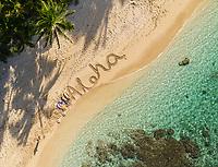 "Aerial view of a family lying next to their message of ""Aloha"" at Mokule'ia Beach near Crozier Drive, Waialua, O'ahu."